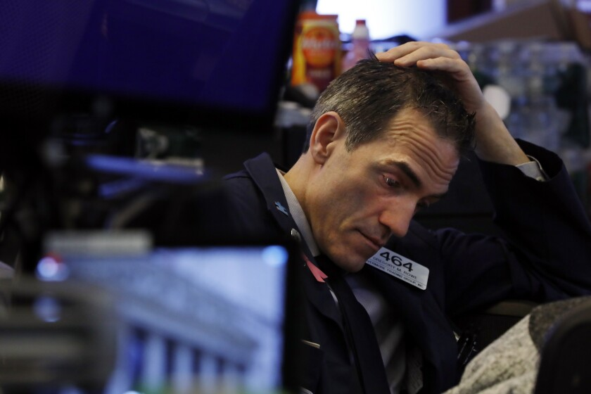 Trader Gregory Rowe prepares for the day's activity on the floor of the New York Stock Exchange, Monday, March 9, 2020. Trading in Wall Street futures has been halted after they fell by more than the daily limit of 5%. (AP Photo/Richard Drew)