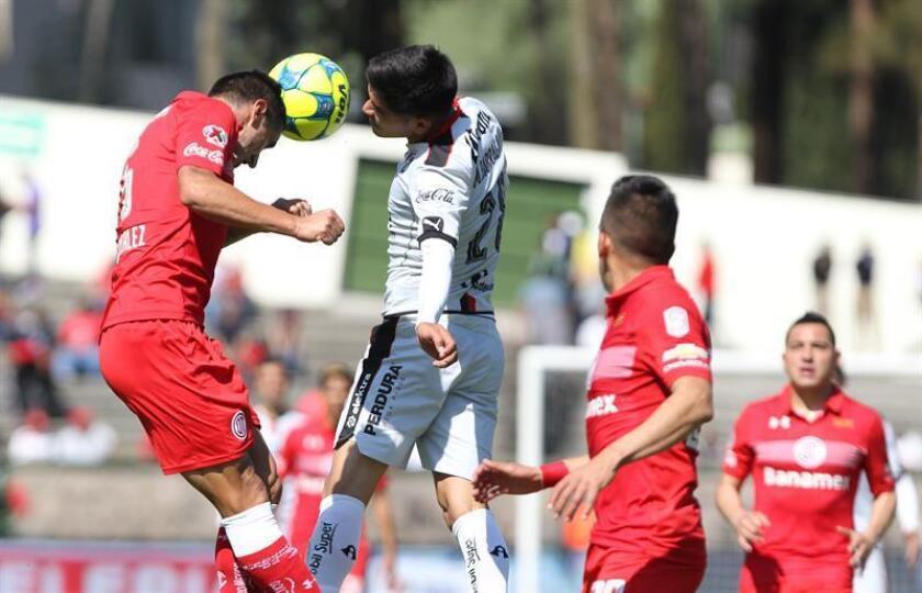 El jugador del Toluca Alexis González (i) disputa un balón ante Martin Barragán (d) del Atlas hoy, domingo 8 de enero de 2017, durante el partido correspondiente a la jornada 1 del Torneo de Clausura 2017, celebrado en el estadio Alberto Chivo Córdoba de Toluca (México). EFE