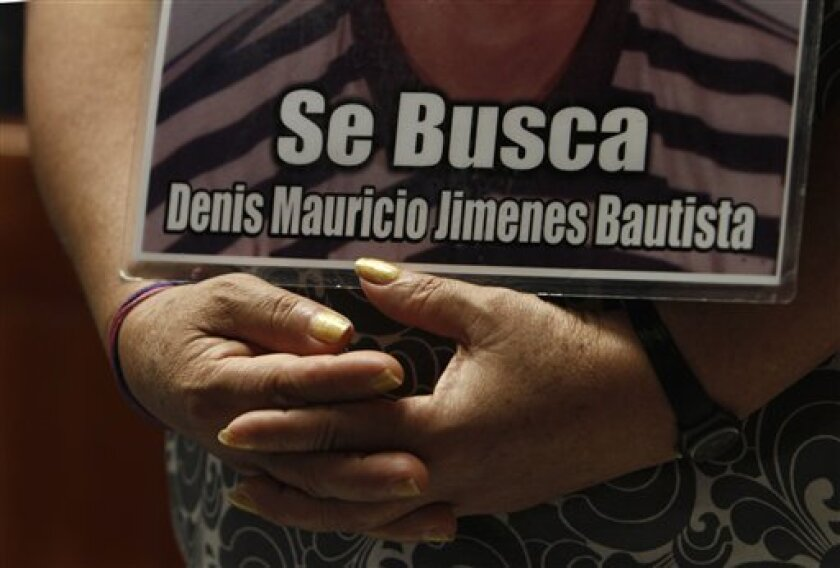 FILE - In this Oct. 28, 2012 file photo, a member of a caravan of Central American mothers hold a photograph of her disappeared child during a Mass at the Basilica of Guadalupe in Mexico City. (AP Photo/Marco Ugarte, file)