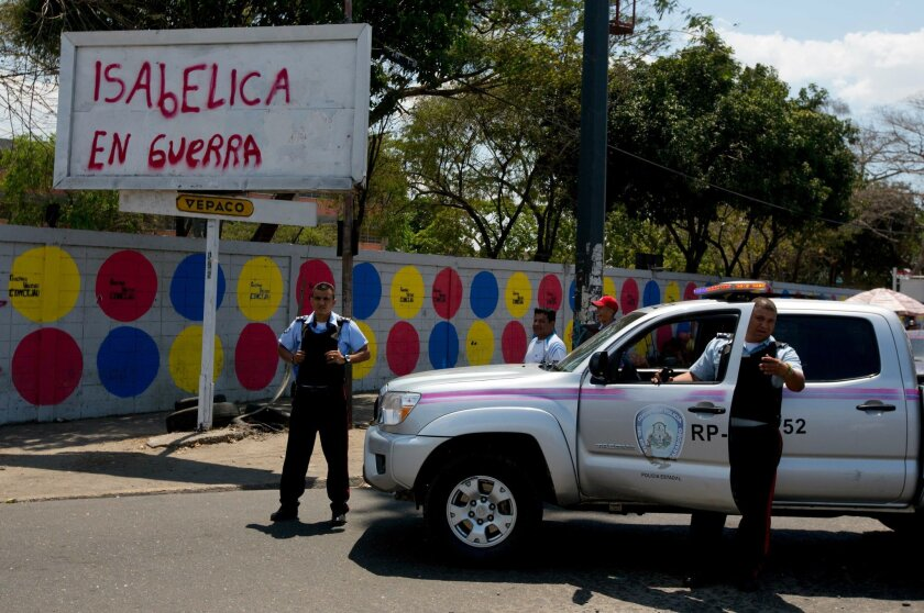 "In this photo taken on Saturday, March 15, 2014. Carabobo's State police officers stand next to graffiti that reads in Spanish ""Isabelica in war""  during a opposition protest at Isabelica neighborhood outside Valencia , Venezuela. The people of the poor district of La Isabelica were made to pay for"
