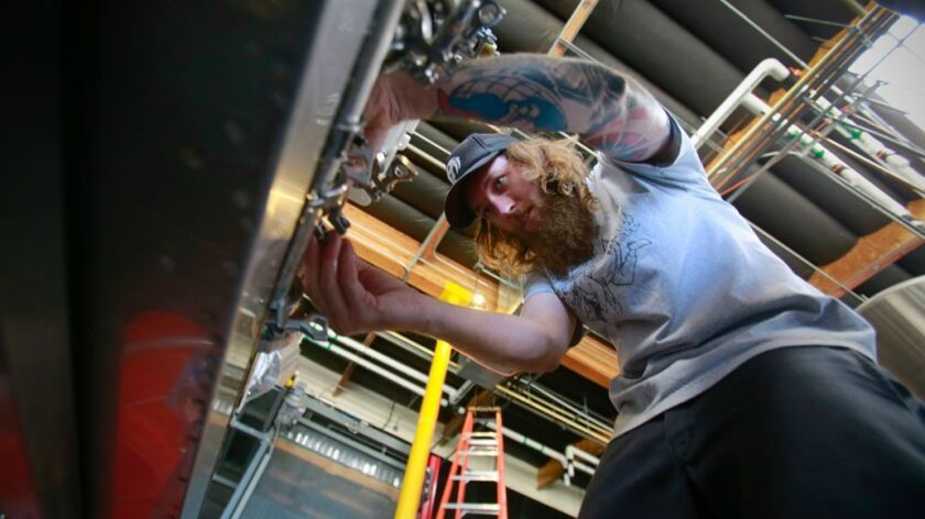 """Ben """"Shaggy"""" Blaney prepares the canning machine at the Mason Ale Works brewery, part of the new Urg"""