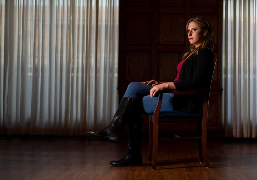 Former Rep. Katie Hill poses seated in profile in front of a black backdrop