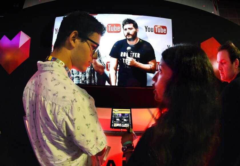 "Visitors to the Electronic Entertainment Expo in downtown L.A.'s convention center on June 17 stand in front of a display promoting YouTube's venture into game streaming called ""YouTube Gaming."""