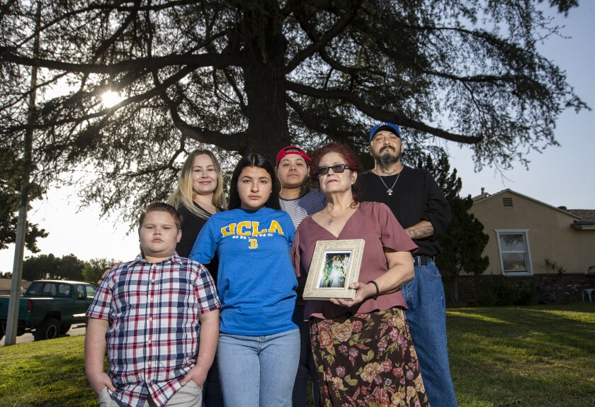Jennifer Soto, in a UCLA shirt, is shown in Downey with her family, from left: Zack Pack; Rose Pack; Sara Bernard; Chris Bernard, holding her 1988 wedding photo of her and her husband, Alex Bernard; and Ismael Moreno.