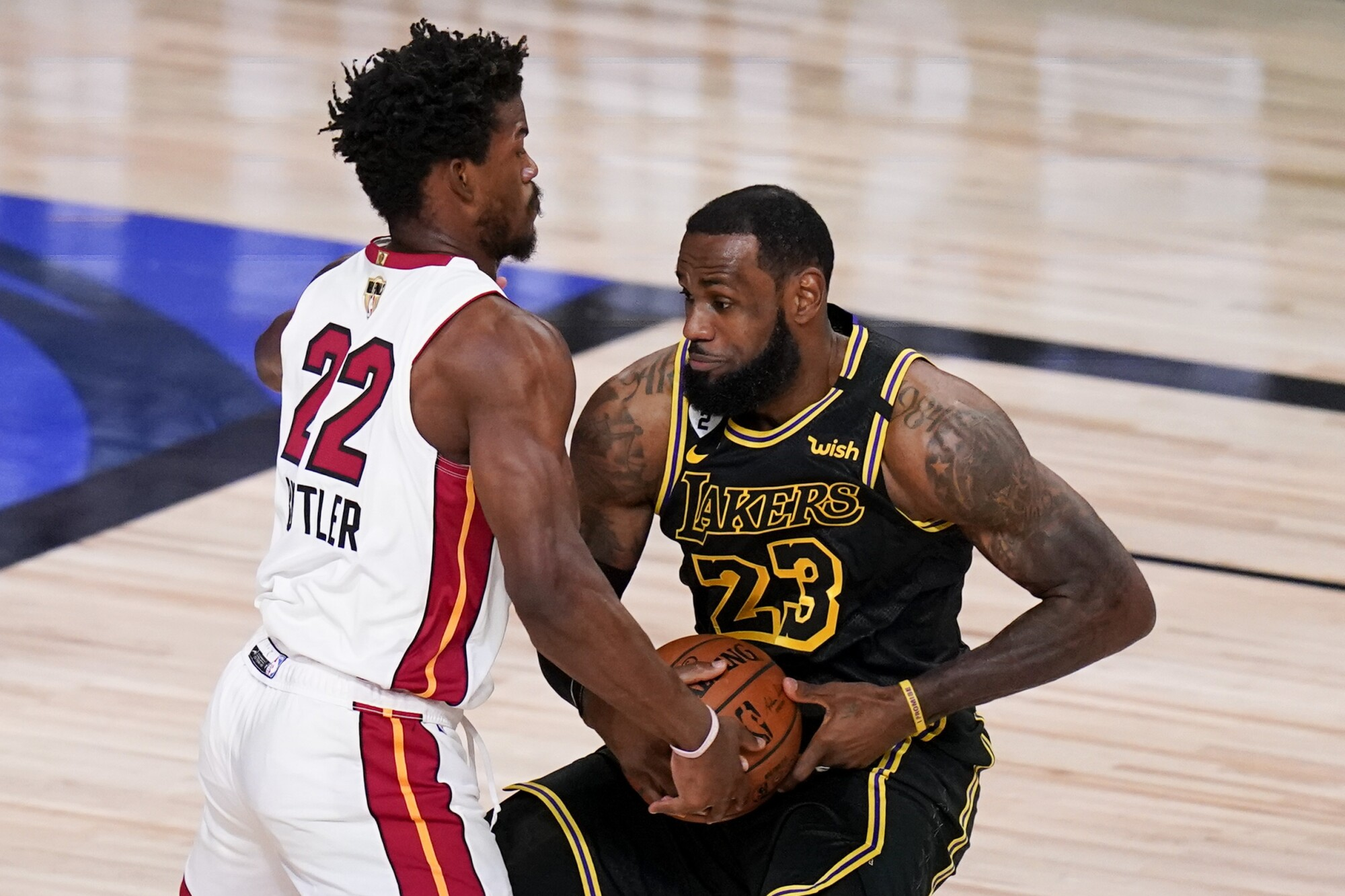 Heat forward Jimmy Butler tries to steal the ball from Lakers forward LeBron James during Game 5 on Friday night.