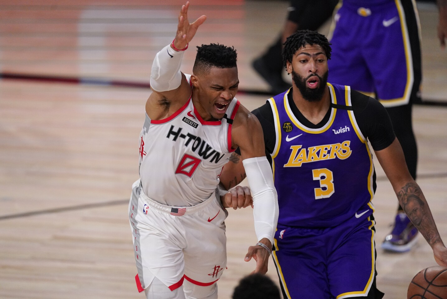 The Rockets' Russell Westbrook, left, loses the ball while being defended by the Lakers' Anthony Davis on Friday.
