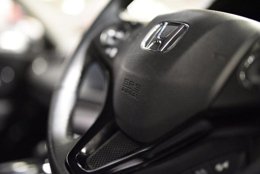 An SRS air bag logo is seen on the steering wheel of a Honda vehicle. Safety regulators fined Honda for not properly reporting problems with defective air bags and other defects.