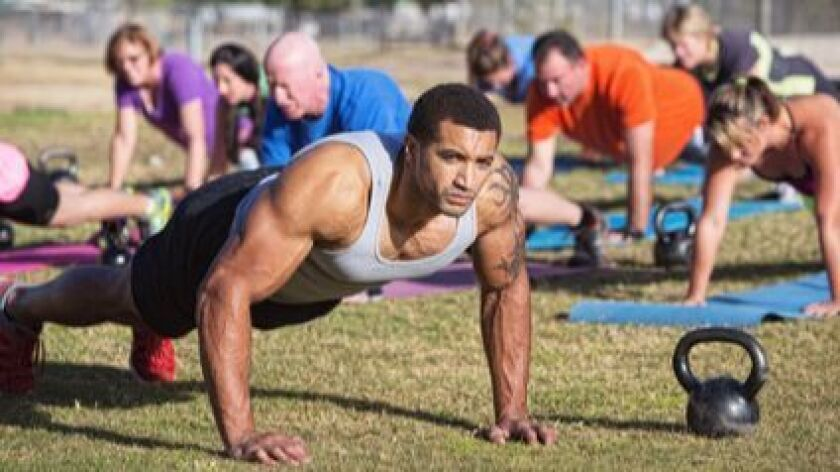 Group of serious adults doing push-ups outdoors.