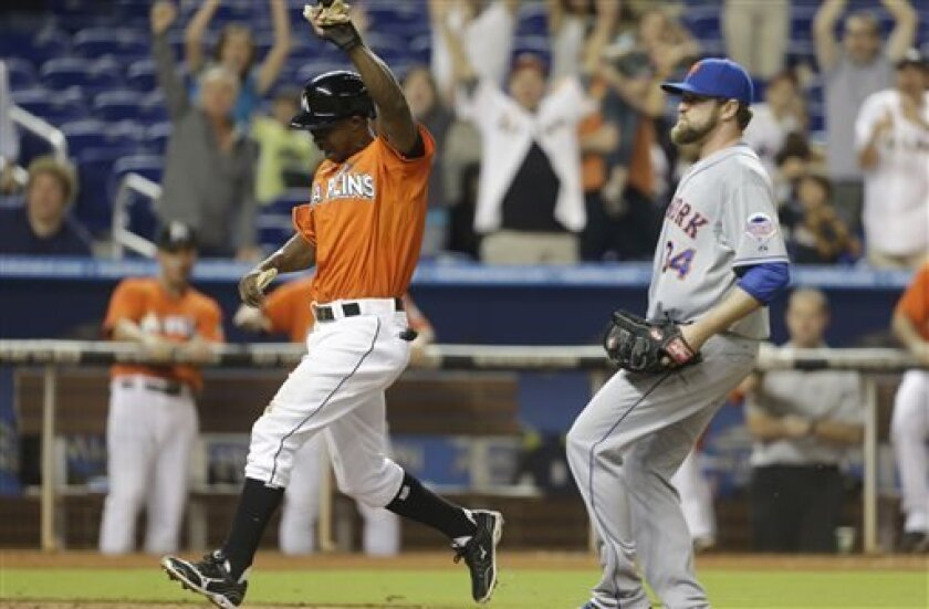 Miami Marlins' Juan Pierre, left, scores the game-winning run on a wild pitch by New York Mets relief pitcher Brandon Lyon (34) in the ninth inning during a baseball game, Tuesday, April 30, 2013, in Miami. The Marlins defeated the Mets 2-1. (AP Photo/Lynne Sladky)
