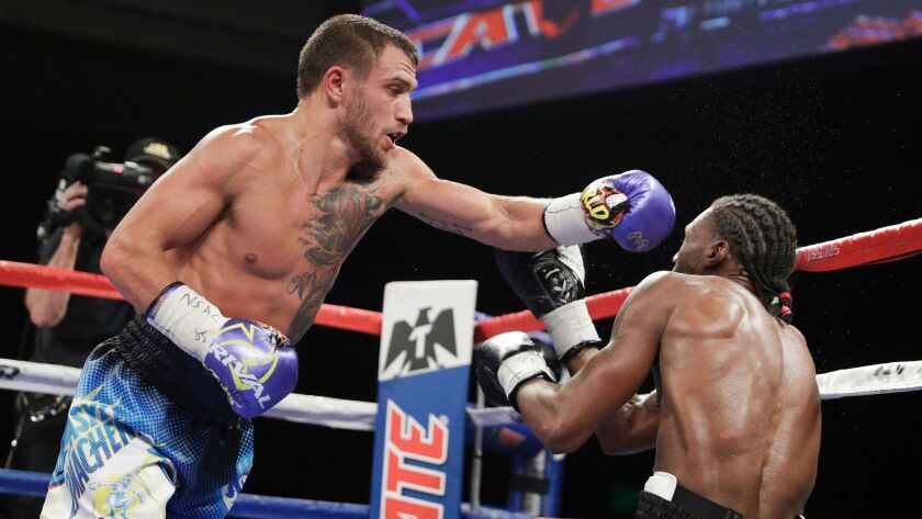 Vasyl Lomachenko, left, hits Nicholas Walters during a WBO junior lightweight title fight on Nov. 26, 2016, in Las Vegas.