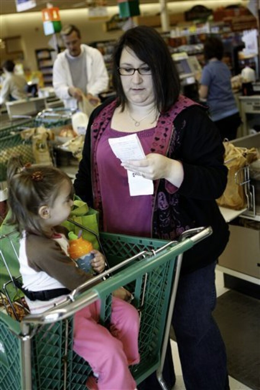 Karen Wilmes of Hopkinton, R.I. checks out her savings while her daughter, Allison, waits, during a shopping trip on Thursday, Oct. 1, 2009 in Westerly, R.I. By purchasing items on sale, using her loyal customer card and coupons, Wilmes saved $54.54, spending only $39 on $93.54 worth of groceries. (AP Photo/Joe Giblin)