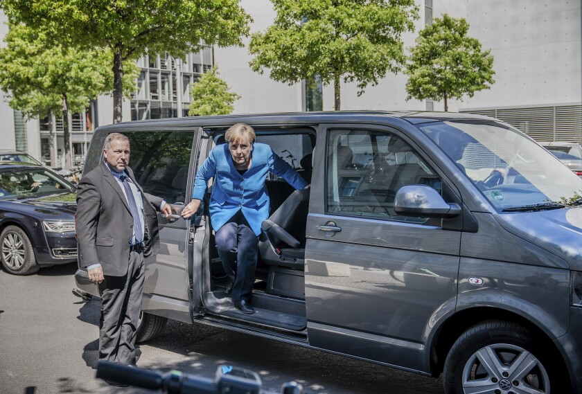 Chancellor Angela Merkel arrives for a legislative session at the Reichstag building in Berlin. To maintain social distancing, she is chauffered by minivan.