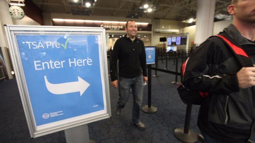 Passengers walk through the TSA PreCheck lane at Milwaukee's Mitchell International Airport. A survey of travelers found that nearly half of TSA PreCheck travelers say the lines are too long. (Mike De Sisti / Associated Press)
