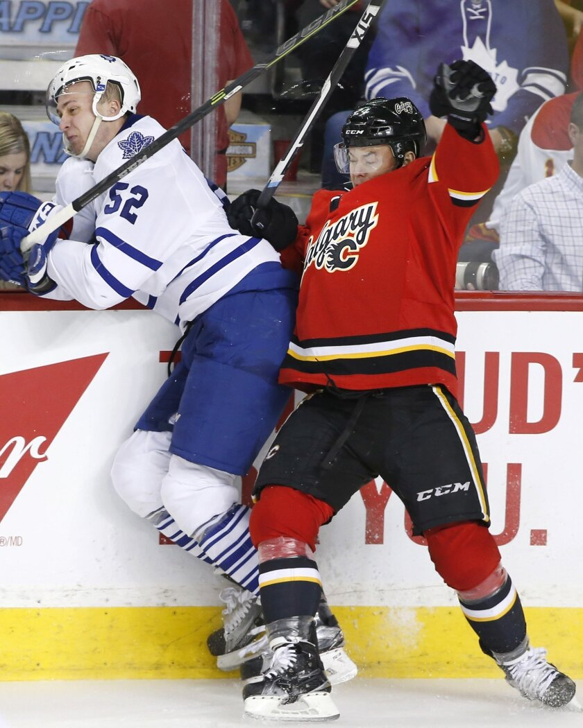 Toronto Maple Leafs' Martin Marincin, left, from Slovakia, is hit by Calgary Flames' Jiri Hudler, from Czech Republic, during second period NHL action in Calgary, Alberta, Tuesday, Feb. 9, 2016. (Larry MacDougal/The Canadian Press via AP) MANDATORY CREDIT