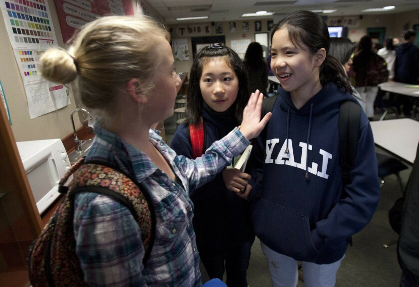 Lincoln Middle School student Avery Ringlever works with Chinese exchange students Zhou Qi Yu, center, and Li Yu Huan, as they change classes at the school Tuesday.
