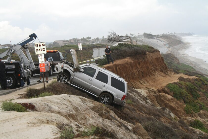 Junior Seau's car is pulled up from the bottom of a cliff in Carlsbad Monday morning.