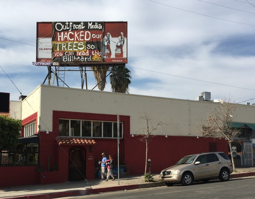 A banner was placed over a billboard above El Condor restaurant on Sunset Boulevard in Silver Lake. Activists have criticized the billboard company, Outfront Media, for cutting back several trees without city permits.
