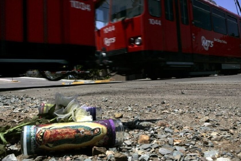 Memorial candles and flowers were left near the  site of a fatal trolley collision Sunday at L Street  in Chula Vista.