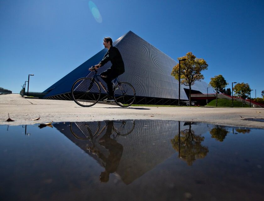 A student bikes past the Walter Pyramid at Cal State Long Beach. This fall, the vast majority of CSU classes will be online only.