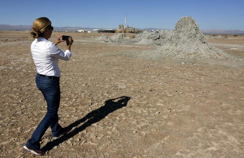 Attorney Maria C. Severson, whose firm has represented the Imperial Irrigation District on energy matters, snaps a picture of the mud mounds formed by the geothermal energy beneath the surface near the Salton Sea in Southern California's Imperial Valley.