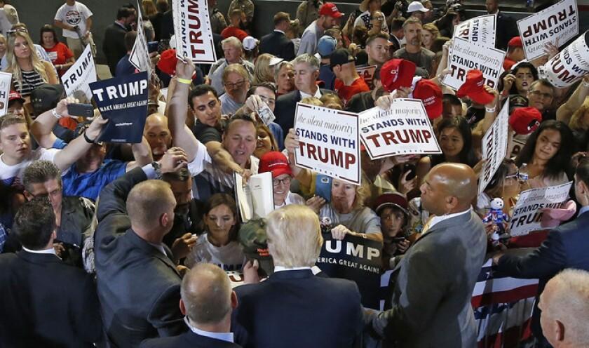 """Donald Trump, casi seguro candidato republicano a la presidencia, firma autÛgrafos tras hablar en un mitin el s·bado 18 de junio de 2016, en Phoenix. Trump insinuÛ el domingo 19 de junio de 2016 que Estados Unidos deberÌa considerar """"seriamente"""" etiquetar por su apariencia fÌsica a los musulmanes dentro del paÌs como una herramienta contra el terrorismo, el ejemplo m·s reciente en que el casi seguro nominado a la presidencia por el Partido Republicano apoya cada vez m·s posturas que podrÌan resaltar a un grupo en especial con base en su religiÛn. (AP Foto/Ross D. Franklin)"""