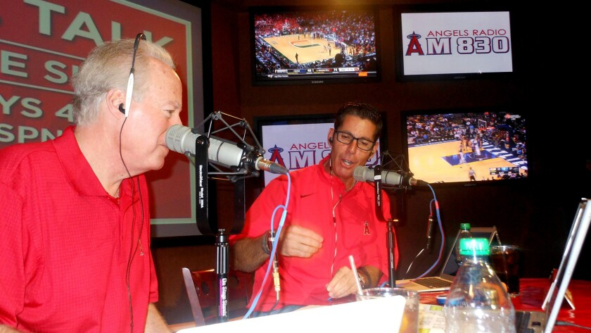 Broadcasters Terry Smith, left, and Victor Rojas talk to fans during a call-in show on 830 AM.