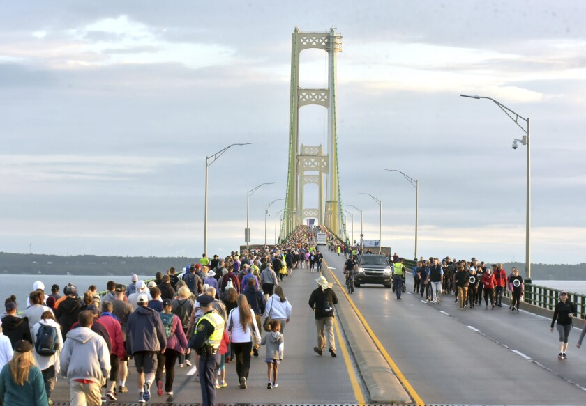 FILE - In a Sept. 2, 2019, file photo, pedestrians walk the Mackinac Bridge on during the 62nd annual Labor Day Bridge Walk in Mackinaw City, Mich. A bomb scare closed the bridge connecting Michigan's two peninsulas for about three hours on Sunday afternoon, July 18, 2021, authorities said. The Mackinac Bridge Authority said nothing was after an extensive search. (AP Photo/John L. Russell, File)