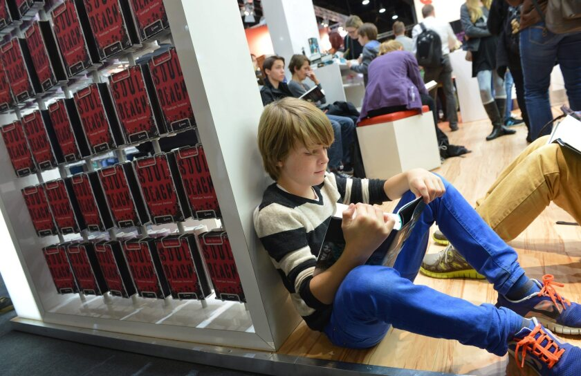 A young reader with a printed book at the Frankfurt Book Fair.