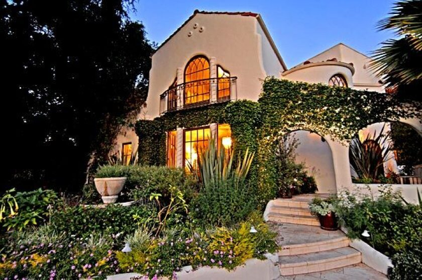 The Spanish-Colonial Revival house presents a fanciful facade with arches and odd-angled doors and windows.