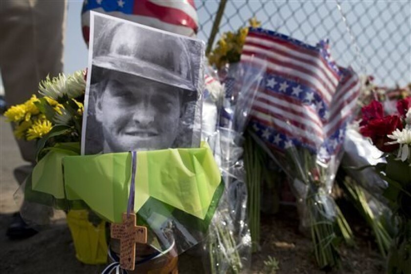A photo of one of the 19 Granite Mountain Hot Shot crew members who was killed fighting a wild land fire near Yarnell, Ariz. on Sunday, sits at a makeshift memorial outside the crew's fire station, Monday, July 1, 2013 in Prescott, Ariz. An out-of-control blaze overtook the elite group of firefighters trained to battle the fiercest wildfires, killing 19 members as they tried to protect themselves from the flames under fire-resistant shields. The disaster Sunday afternoon all but wiped out the 20