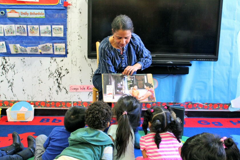 """In this 2018 photo provided by Children's Aid, Nina Crews, illustrator of """"A Girl Like Me,"""" reads to children at an early childhood education center. Crews said the work of independent publishers and grassroots organizers are vital in bringing more racial diversity into children's books. (Adriana Alba/Children's Aid via AP)"""