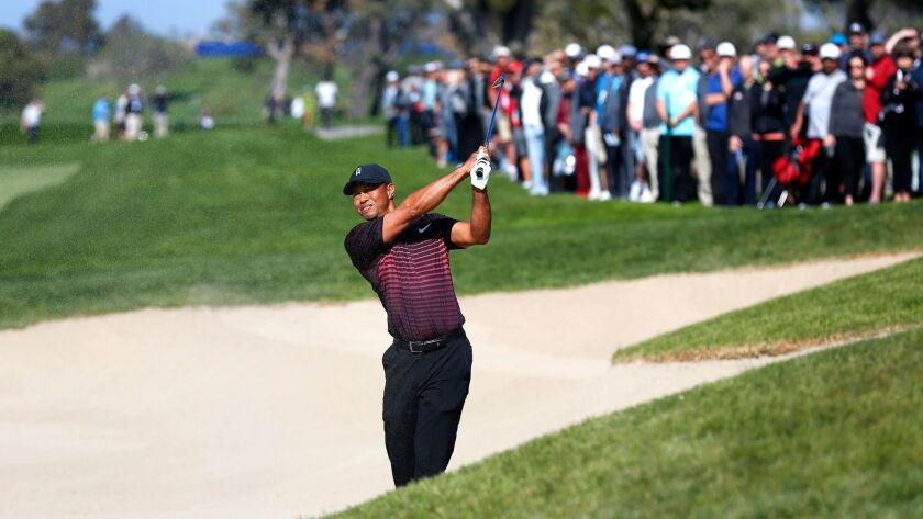 Tiger Woods hits out of the sand on the 5th hole of Torrey Pines South during the first round of the Farmers Insurance Open on Thursday.
