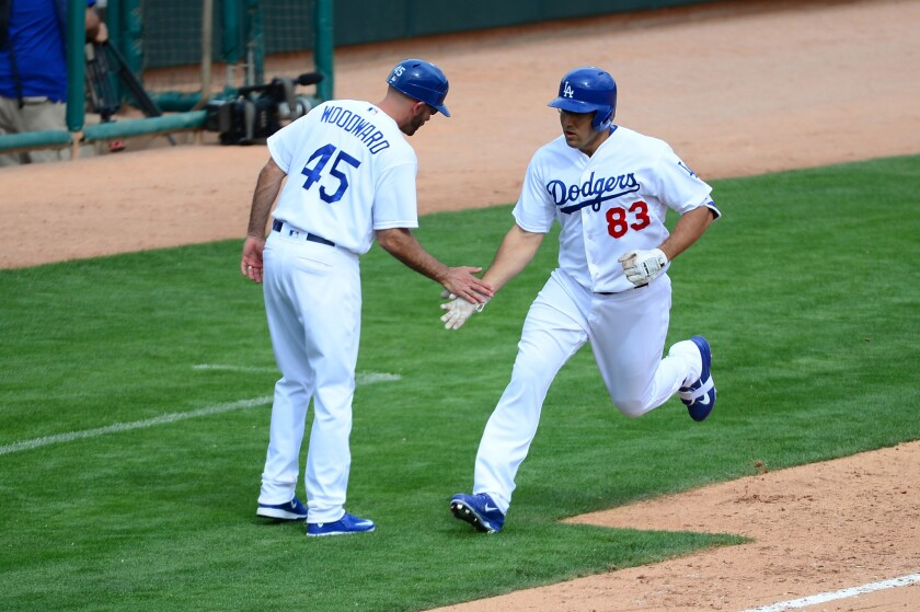 Dodgers third base coach Chris Woodward congratulates Rob Segedin after his two-run home run against the Diamondbacks during a spring training game on March 5.