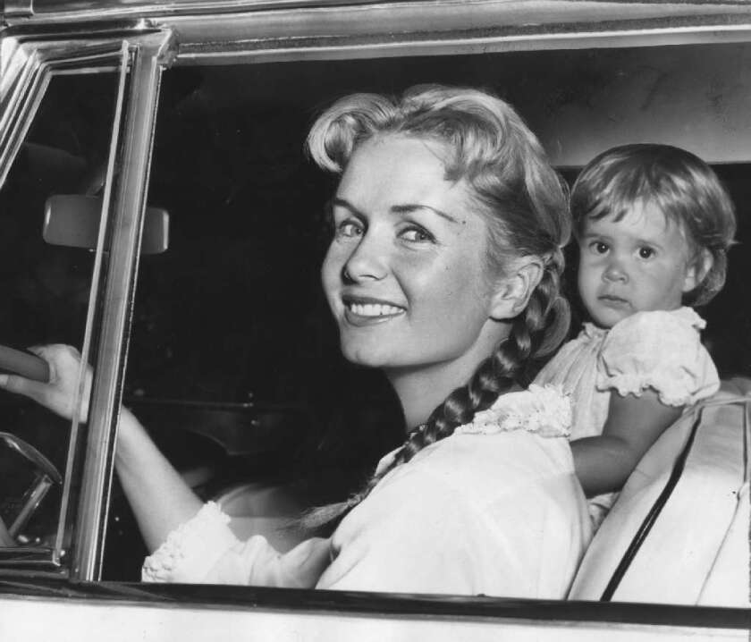 Debbie Reynolds, with her daughter, Carrie, 23 months, smiles as she leaves the house on Sept. 9, 1958, to visit friends. Husband Eddie Fisher and Reynolds later revealed their separation.