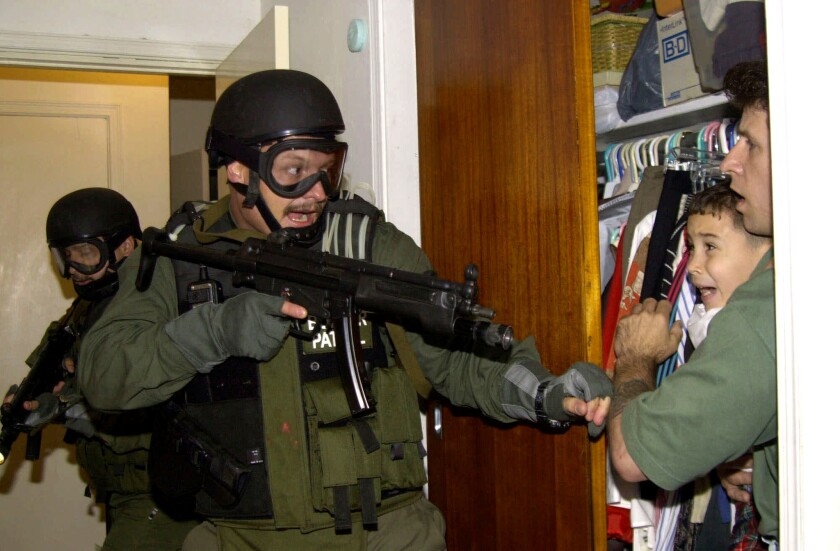 Pulitzer-winning April 22, 2000, photo shows Elian Gonzalez being held in a closet as government officials come to get the young boy in Miami to be returned to his dad in Cuba.
