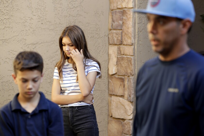 FILE - In this Nov. 5, 2019, file photo, Madelyn Staddon, center, listens along with her brother Connor Staddon, left, while their father, Aaron Staddon, right, a relative of some of the members of a Mormon community who were attacked while traveling near the U.S.-Mexico border, speaks from his home in Queen Creek, Ariz. Madelyn was so affected by the extended family's loss that she created a digital tribute to be shared. (AP Photo/Matt York, File)