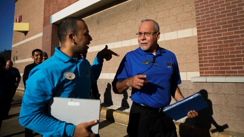 Steve Pacheco tests his sales pitch with coworker Hugo Chavez, right, as Best Buy employees practice for Black Friday in Atwater Village.