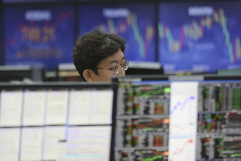 A currency trader watches monitors at the foreign exchange dealing room of the KEB Hana Bank headquarters in Seoul, South Korea, Monday, June 22, 2020. Shares were mostly higher in Asia on Monday despite reports that the number of coronavirus cases in the U.S. has surged sharply. (AP Photo/Ahn Young-joon)