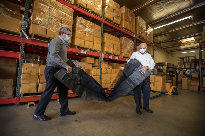 David Cameron, left, vice president, and Abdul Salam, president of Salam International, unpack a body bag.