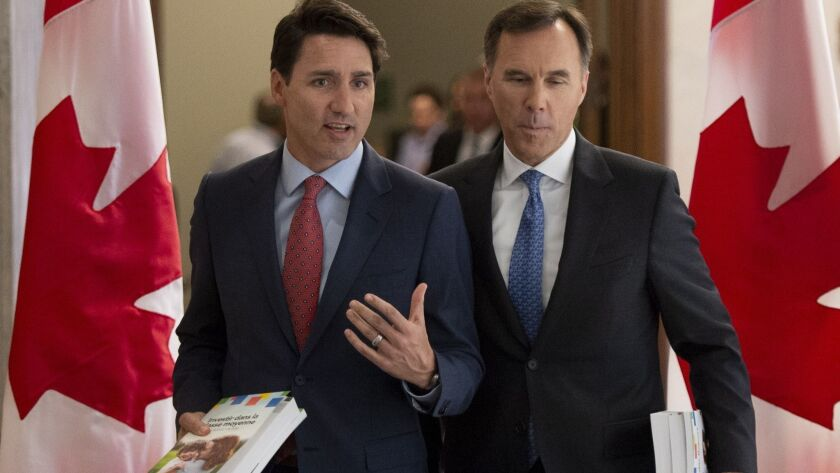 Prime Minister Justin Trudeau and Finance Minister Bill Morneau speak as they walk to the House of C