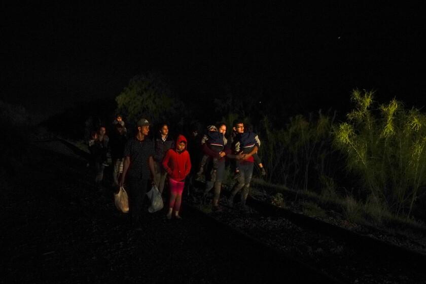 Un grupo de personas con hijos en sus brazos llega a un centro de procesamiento de migrantes