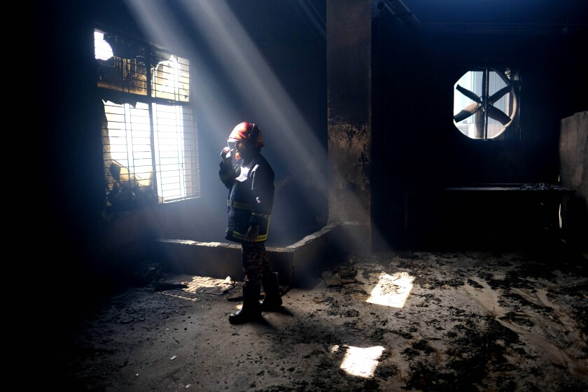A firefighter communicates with his colleagues on a walkie talkie inside the burnt food and beverage factory in Rupganj, outside Dhaka, Bangladesh, Friday, July 9, 2021. At least 52 people died in a huge blaze that engulfed a food and beverage factory outside Bangladesh's capital, fire officials said Friday, in the latest industrial disaster to hit the South Asian nation. (AP Photo/Mahmud Hossain Opu)