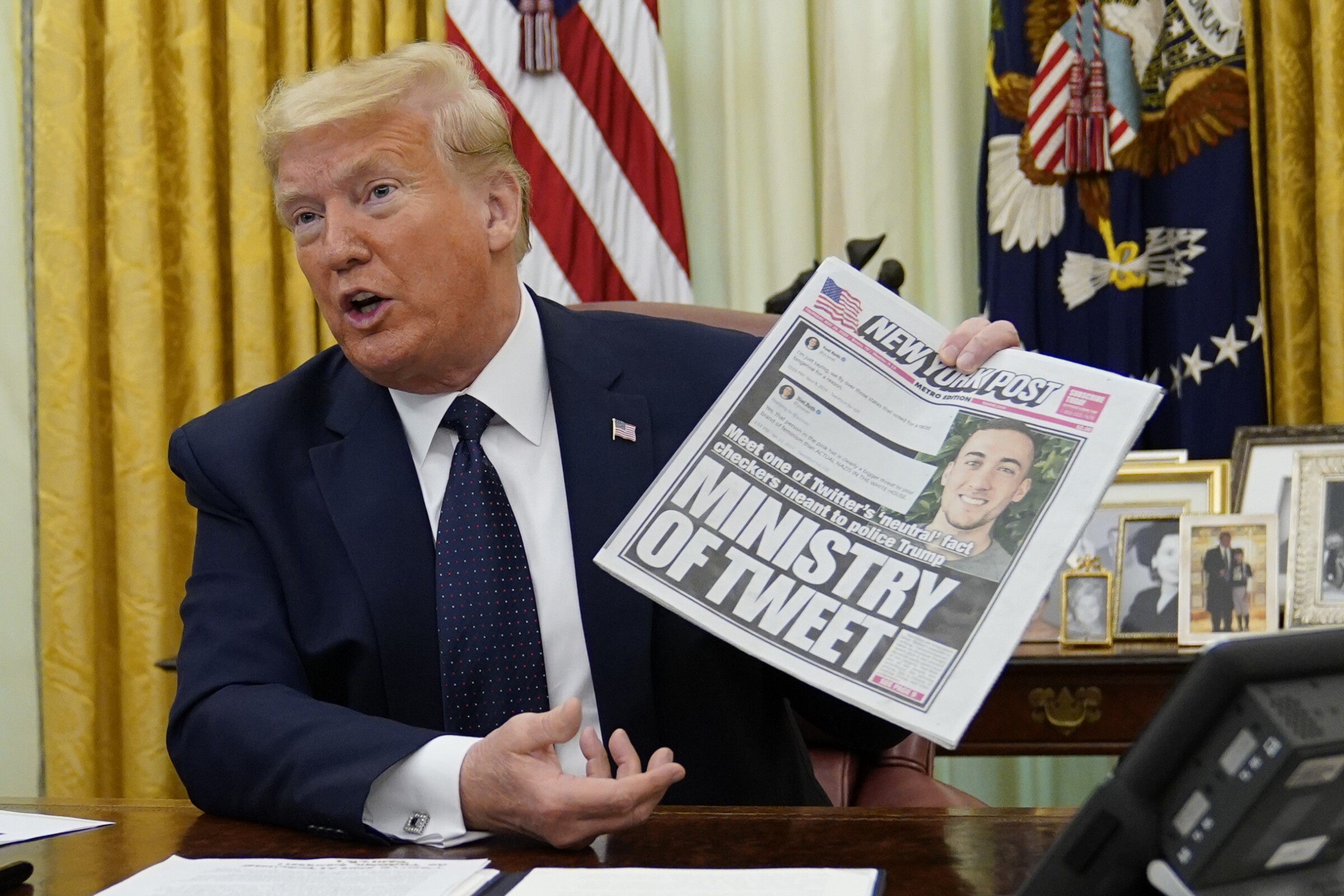 President Trump holds up a copy of the New York Post at the White House before signing an executive order aimed at curbing protections for social media giants.