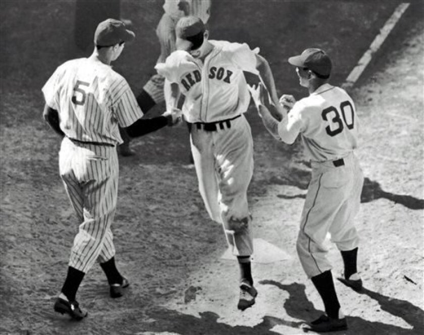 FILE - In this file photo made July 8, 1941, Ted Williams, center, is greeted at home plate by teammate Joe DiMaggio (5) and coach Marv Shea after hitting a dramatic ninth-inning home run to give the American League a 7-5 victory over the National League in the All-Star Game at Briggs Stadium in De
