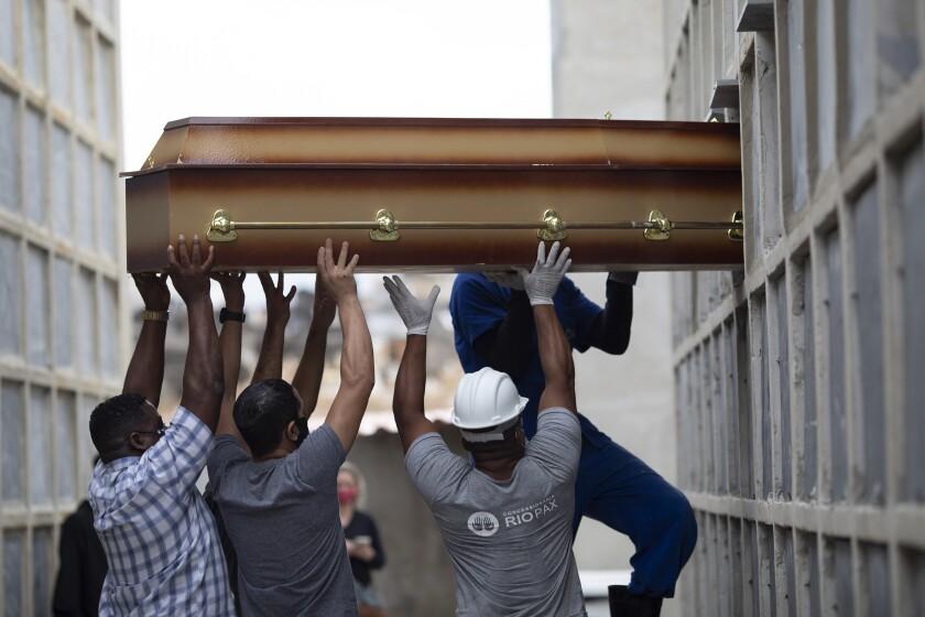 Operarios y familiares introducen el féretro con los restos de una mujer que murió por complicaciones
