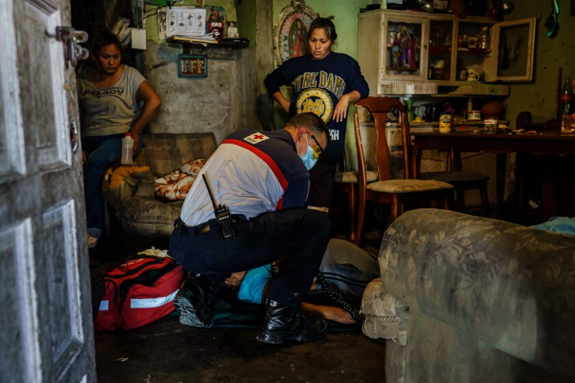 Red Cross paramedic Sergio Garcia checks for a pulse as he tries to resuscitate Maria Ruiz Olmedo, 71, as family members watch at their Tijuana home in April 2020.