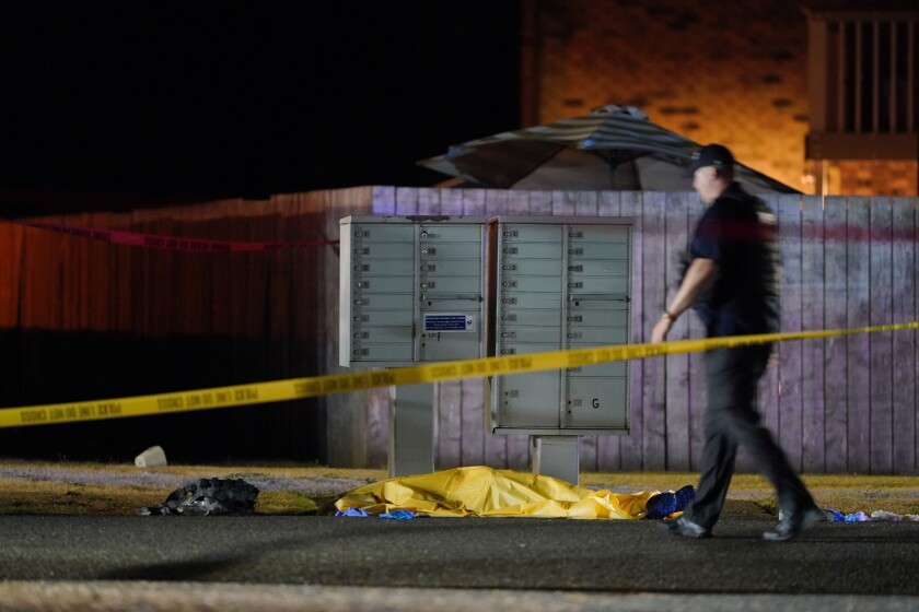 A tarp covers a body in Lacey, Wash., after agents killed a suspect in the death of a right-wing protester in Portland, Ore.
