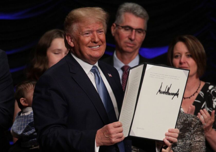President Trump displays an executive order he signed Wednesday.