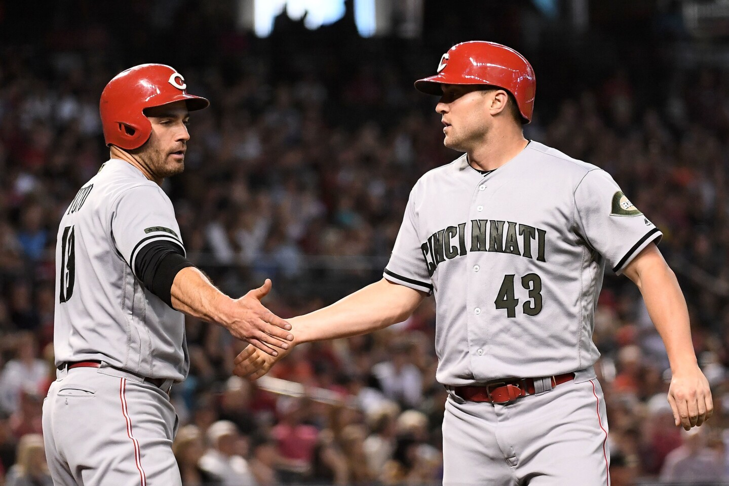 PHOENIX, AZ - MAY 28: Scott Schebler #43 of the Cincinnati Reds is congratulated by Joey Votto #19 after scoring against the Arizona Diamondbacks in the fifth inning of the MLB game at Chase Field on May 28, 2018 in Phoenix, Arizona. MLB players across the league are wearing special uniforms to commemorate Memorial Day. (Photo by Jennifer Stewart/Getty Images) ** OUTS - ELSENT, FPG, CM - OUTS * NM, PH, VA if sourced by CT, LA or MoD **