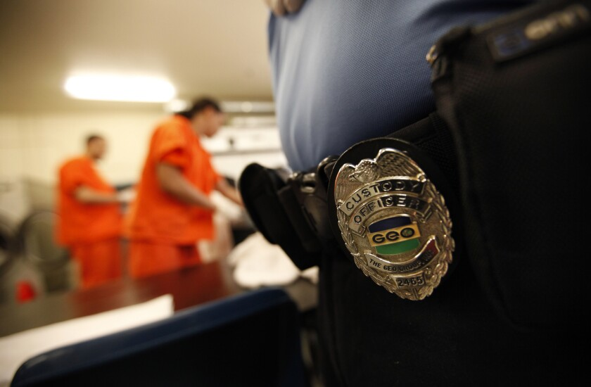 A guard watches inmates fold clothes at the Mesa Verde ICE Processing Facility in Bakersfield.